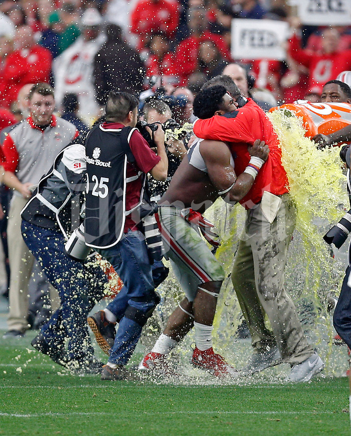 Ohio State Buckeyes running back Ezekiel Elliott (15) holds Ohio State Buckeyes head coach Urban Meyer as he gets gatorade poured on him against Notre Dame Fighting Irish in the fourth quarter during the Fiesta Bowl in the University of Phoenix Stadium on January 1, 2016.  (Dispatch photo by Kyle Robertson)