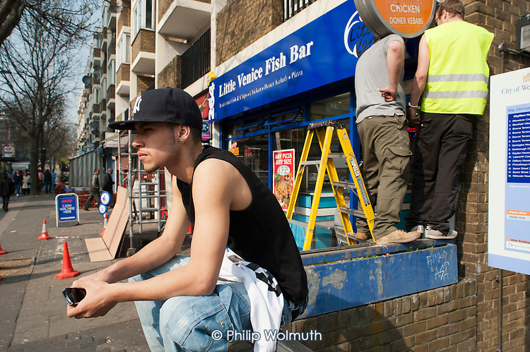 Young man sitting on a wall on the Harrow Road, West London, close to the much wealthier district of Little Venice.