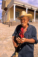 Portrait of traditional Cuban man and rooster in old colonial village, Trinidad, Cuba.
