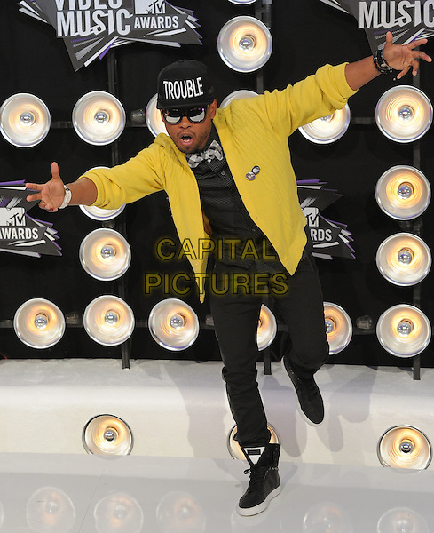 Miguel.Arrivals at the 2011 MTV Video Music Awards held at Nokia Theatre L.A. Live in Los Angeles, California, USA..28th August 2011.full length black jeans denim yellow jacket sunglasses shades baseball cap hat arms leg up dance dancing gesture mouth open funny.CAP/RKE/DVS.©DVS/RockinExposures/Capital Pictures.