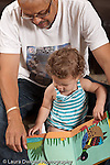 13 month old baby girl at home with father who is her primary caregiver sitting with him read to, looking at picture book vertical
