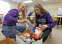 Guerin students helped fill food boxes at St. Maria Goretti for distribution at Thanksgiving.  (l-R) Hannah Miller and Sami Bischof.