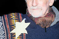 A man wears a cutout of a yellow Star of David while he stands with anti-Trump protesters gather near the Sheraton Portsmouth Harborside Hotel in Portsmouth, New Hampshire, USA. The star is a reference to the stars that Jews were forced to wear under Nazi Germany and also a reference to Trumps idea to ban all Muslims from entering the US. At the hotel later that evening, Republican presidential candidate and real estate mogul Donald Trump received an endorsement from the New England Police Benevolent Association executive council. Many protesters expressed disagreement with Trump's recent statements that he would ban all Muslims from entering the country. Trump brought up the recent shooting in San Berdardino, Calif., at the meeting. A small group of perhaps 20 Trump supporters stood outside the hotel. One of the protest organizers estimated that there were around 230 protesters gathered.