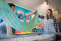 """Artist Marie Haley (from left) and Emily Wright of Fayetteville lift a scarf Wright dyed using a water marbling technique, Sunday, January 12, 2020 during a water marbling class at Art & Soul Studios NWA in Rogers. Check out nwaonline.com/200113Daily/ for today's photo gallery.<br /> (NWA Democrat-Gazette/Charlie Kaijo)<br /> <br /> Marie Haley, artist and owner of Art & Soul Studios, lead a class to show art enthusiasts an innovative approach to dying fabrics. The water marbling technique is from the 15th century. Artists drop paints into a bath of seaweed solution that rises to the top. Afterwards, they use tools to create designs with the paint before dipping their fabric into the bath. <br /> <br /> Visitors who tried the art style shared their experience of the process saying, """"This is satisfying because you can't mess up. It doesn't take that long. You get instant gratification."""" And """"What it turns out to be might not be what you expected."""""""