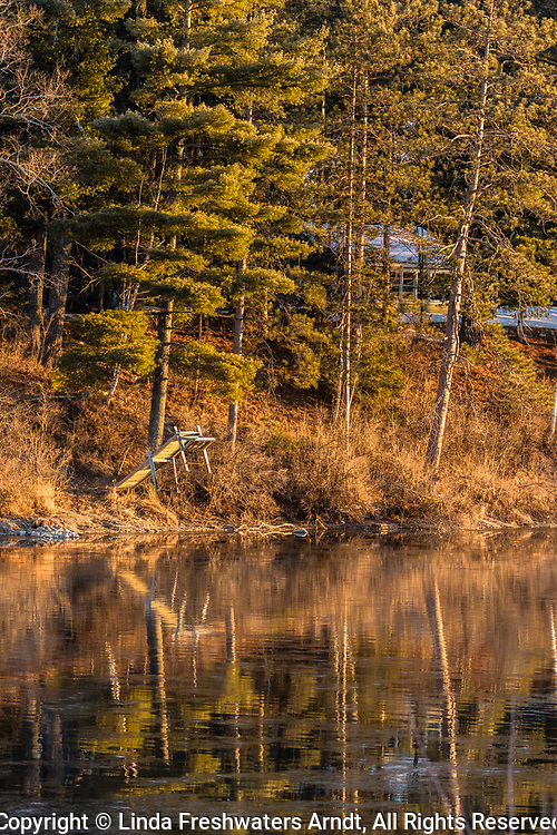 Early morning sunrise on the Chippewa river in northern Wisconsin.  A seasonal resort is the background with some snow still remaining on the ground with some time remaining before the dock is placed back in the water and the resort is open for summer tourists.
