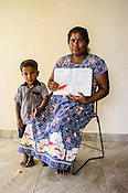 Sri Lankan woman poses for  photo with their child and the CHDR- Child Health Development Record Card (immunization/vaccination card) in the Ministry of Health office in Tharmapuram Village in Kilonochchi, Sri Lanka.  Photo: Sanjit Das/Panos