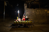 A watermelon seller waits for customers at the bottom of Shibati, or 18 Steps, in central Yuzhong district, Chongqing, China.