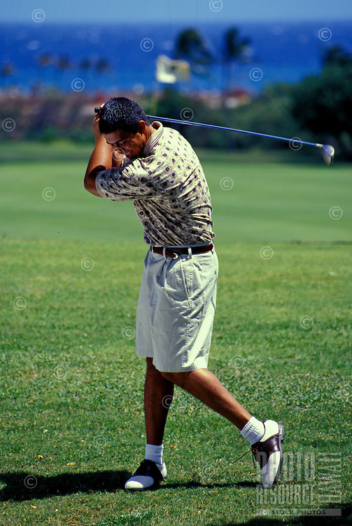 Young local man playing at Kokohead golf course, Oahu