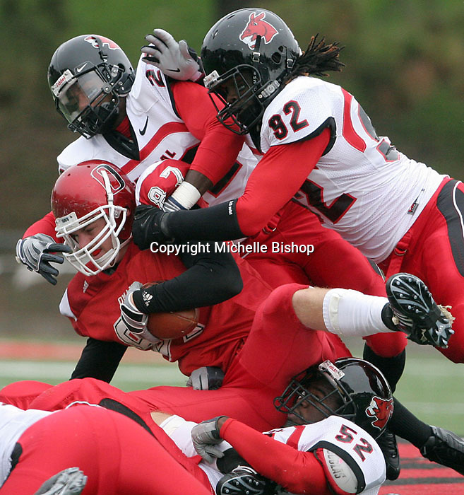 Central Missouri 's Deonte Ball (left) and Jeremy Wallace (right) bring down UNO's Mike Higgins during Saturday's game.