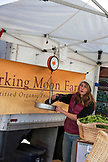 USA, Oregon, Ashland, farmer from the Barking Moon Farm weighs produce, the Rogue Valley Growers and Crafters Market