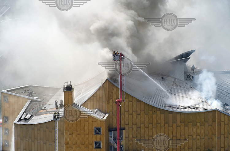 Smoke rising from the roof of the building housing the Berlin Philharmonic near Potsdamer Platz, after it caught fire during a rehearsal. The building, built in the 1960s, is believed to have had the best acoustics in the world.