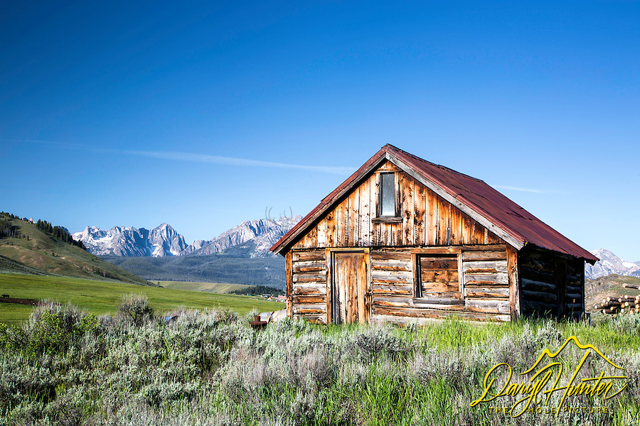 A derelict cabin stands proud at the foot of the Sawtooth Mountains of Stanley Idaho.