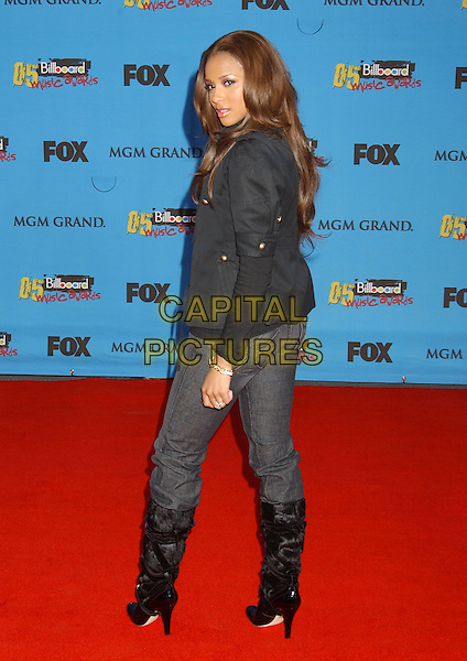 CIARA.2005 Billboard Music Awards held at the MGM Grand Hotel & Casino, Las Vegas, Nevada..December 6th, 2005.Photo: Laura Farr/AdMedia/Capital Pictures.Ref: LF/ADM.full length black jacket jeans denim boots looking over shoulder.www.capitalpictures.com.sales@capitalpictures.com.© Capital Pictures.