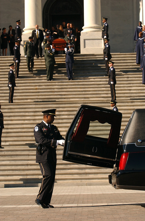 An officer opens the door of a hearse as the casket containing the body of civil rights activist, Rosa Parks, is brought out of the East Front of the Capitol after laying in honor on Sunday and Monday.