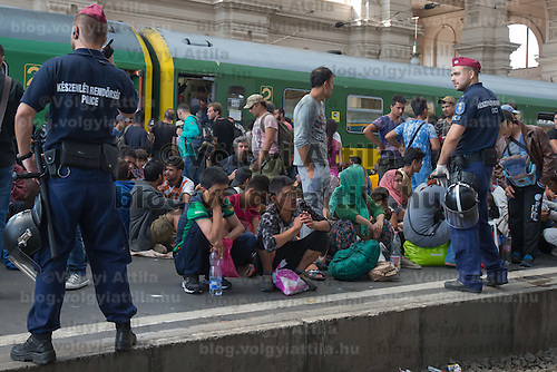 Illegal migrants sit on the platform as they wait under police supervision to board a train in hopes to leave for Germany at the main railway station Keleti in Budapest, Hungary on September 03, 2015. ATTILA VOLGYI