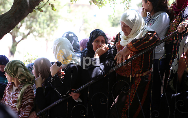 Relatives of 21-year-old Palestinian Abdallah Ghanayem, mourn during his funeral in the village of Kafr Malik, northeast of Ramallah on June 14, 2015. An army spokesman said that the Palestinian had died after he threw an incendiary device at a jeep and the vehicle overturned on him. Palestinian security sources said, Israeli soldiers killed Ghanayem by hitting him with their jeep during clashes near Ramallah in the occupied West Bank. Photo by Shadi Hatem
