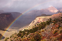 A November storm produces a rainbow arching towards the rock formation Angels Gate.  Seen from the lower section of the Grandview trail just above Horseshoe Mesa in Grand Canyon National Park.
