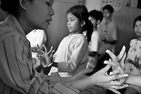 Children of Bassac. Teacher Nop Thyda is adjusting hand position. The articulation must be streched while the dancers are young. Legs, wrists, elbows, fingers, each part of the body is made more supple until  getting un-naturel moves. Phnom Penh, Cambodia - 2005