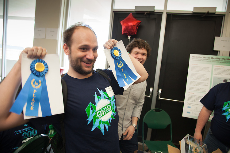 Elijah Rippeth dances with his teams first place ribbons after being awarded for their work on a remote water quality monitoring system, at the annual Student Research and Creative Activity Expo at Ohio University.  More than 800 participants from 56 departments and schools took part in the event. Photo by Ohio University / Jonathan Adams