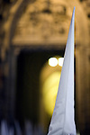 Hooded penitent entering Seville's cathedral, Holy Week, Spain