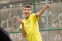 A kid celebrates a goal after playing football at a small pitch in Favela Santo Amaro in the hills around Rio de Janeiro