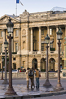 Tourists talking on street corner in front of Hotel de Crillon in Place de la Concorde, Central Paris, France
