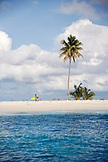 INDONESIA, Mentawai Islands, Kandui Resort, man walking with surfboard on a small island with a palm tree