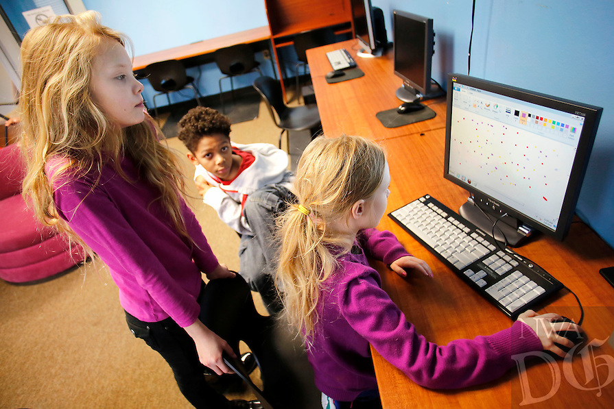 NWA Democrat-Gazette/DAVID GOTTSCHALK  Zoey Davis, 10,  (from left) and Devin Turner, 9, watch her sister Madison Cothran, 8, Monday,  January 4, 2015, use a painting program inside the computer lab at the Yvonne Richardson Community Center in Fayetteville. The center is open Monday - Thursday from 10:00 a.m. - 7:00 p.m., Friday from 10:00 a.m. - 6:00 p.m., and Saturday from 10:00 a.m. - 2:00 p.m. The center offers youth and adult programs and hosts a variety of community events.