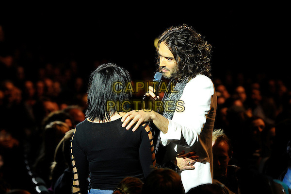 Russell Brand performing his 'Messiah Complex' Show, Eventim Apollo, Hammersmith, London, England. <br /> 14th October 2013<br /> on stage in concert live gig performance half length white suit jacket grey gray scarf beard facial hair side profile fan audience hand on shoulder <br /> CAP/MAR<br /> &copy; Martin Harris/Capital Pictures