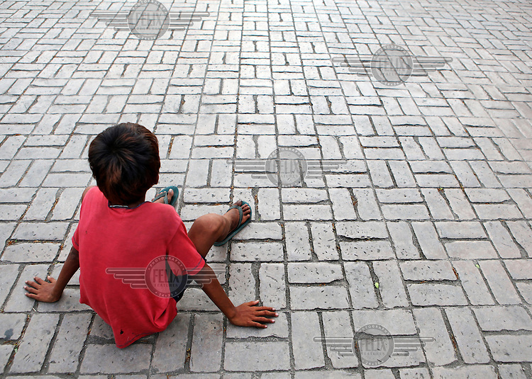12 year old Mark sitting on the ground near one of his begging spots at the Basilica Minore del Sto Nino in Cebu CIty.