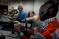 Eye Radio broadcast journalist SANTINO DOMINIC ATEM AND CLEMENT WANI, AKA, DJ LOMISAK,  talk about upcoming music from the Juba station newsroom in South Sudan while Clement Wani, AKA, DJ Lomisak, waits to go on the air. In an effort to build up media and encourage a free media, USAID funded the station which is run by Internews.