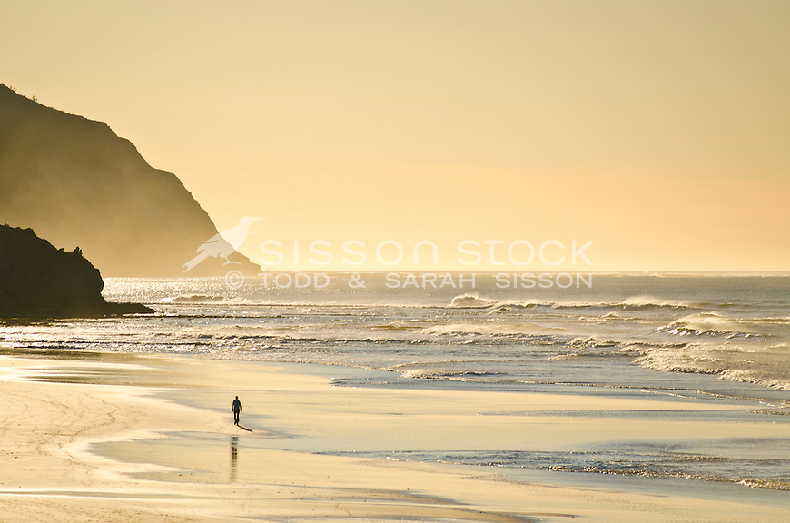 Golden light on breaking waves. Person walking on beach. Gisborne NZ