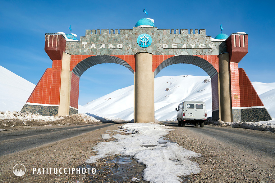 A car passes beneath a huge gate while driving in Kyrgyzstan