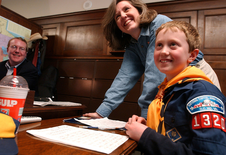 work3/042403 -- Charlie Black, 8, explains his homework assignment to staffers in the office of Rep. Sam Johnson, R-Texas, including mom Kathleen Quint Black and Spencer Ritchie.