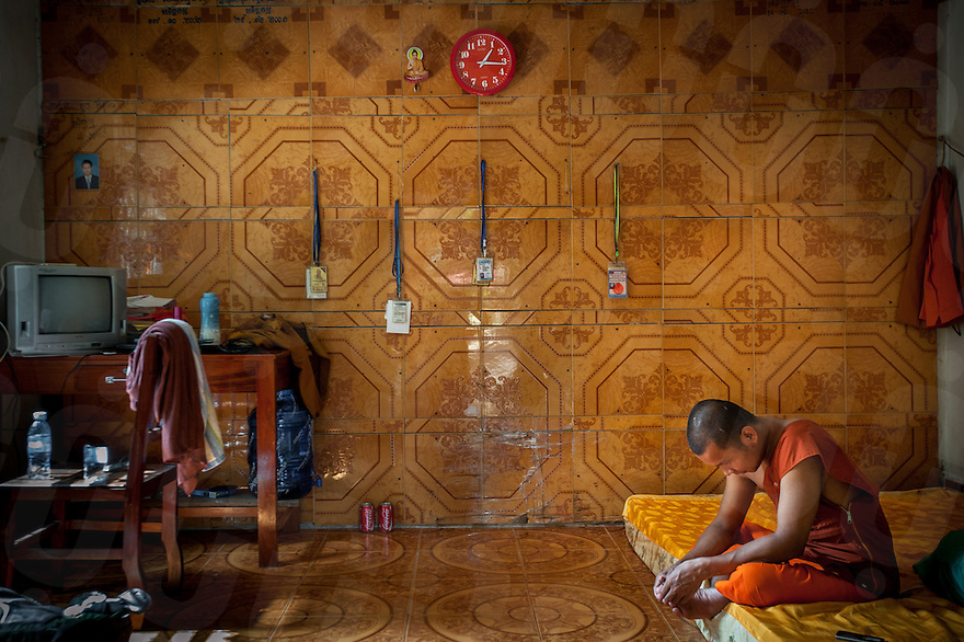 November 28, 2013 - Phnom Penh, Cambodia. A monk sits in his room, with various access passes hanging up on the wall. © Luc Forsyth / Ruom