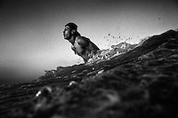22 year old surfer Ibrahim Alamassi breaks through the surf in the Mediterranean Sea off Gaza City.
