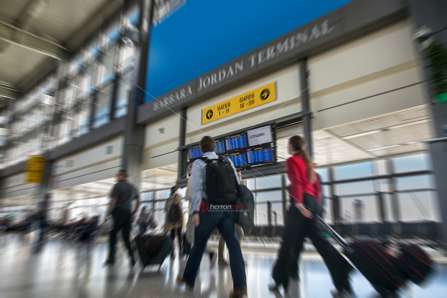 Business travelers rush to their gates past the flight information display monitors in the terminal at Austin's ABIA Airport.