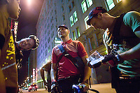 3 July 2005 - New York City, NY, USA - Riders share jokes at an alleycat checkpoint on 43rd street in New York City, USA, July 3rd 2005. Alleycats are urban cycle races held informally - without notification of the authorities - on open roads and in real traffic, to simulate the messenger's working conditions. Photo Credit: David Brabyn<br />