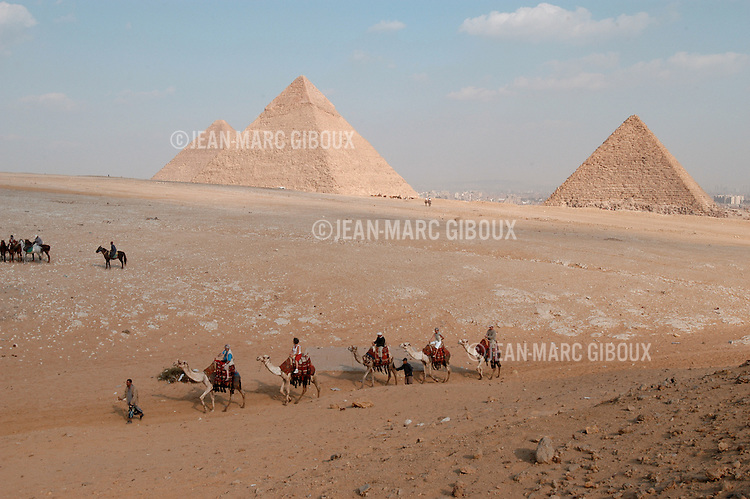 CAIRO - NOVEMBER 30, 2004 : Foreign tourists on a camel train near the 5000 years old Giza pyramids in Cairo, on November 30, 2004. Sitauated high on a desert plateau overlooking sprawling Cairo, Giza is the most visited tourist site in Egypt ,with the Sphinx and the 481ft high great Pyramid. Tourism has been on the decline in Egypt following a series of terrorist attacks targeting foreign tourists. (Photo by Jean-Marc Giboux)