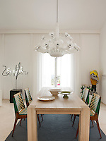 A white, dining room area with a sand-blasted stone floor. A contemporary Leda chandelier hangs above a bespoke bleached oak dining table and chairs. Various pieces of artwork are displayed around the room.