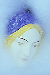 Face of young woman doll wearing cap or bonnet and makeup lying in sheet of ice