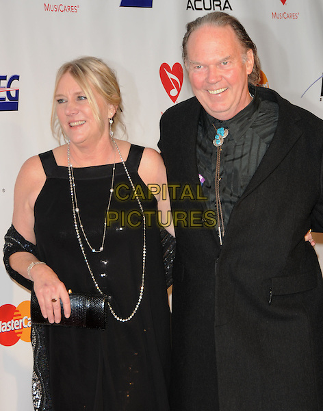 PEGI YOUNG & NEIL YOUNG .at The 2010 Musicares Person of The Year Tribute to Neil Young held at The L.A. Convention Center in Los Angeles, California, USA, January 29th 2010                                                                   .half length black dress couple peggy married husband wife necklace shirt coat grey gray wrap shawl clutch bag .CAP/RKE/DVS.©DVS/RockinExposures/Capital Pictures