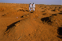 Graves of drought victims in refugee ring outside city of Khartoum.  This refugee ring is the largest in the world--4 million people seek refuge here...Story Summary:.Sudan, the largest country in Africa, hosts a civil war between the Islamic North and the African South that has the highest casualty rate of any war since World War II...Two and a half million people have been killed in this insidious conflict.  It drags on because Southerners have no voice, and the Northerners have engineered ÒThe Perfect WarÓ where none of their people are killed...The North forces people out of the South by bombing them, burning their crops, and harassing them with gunships. They abduct their children and draft them to fight with the Northern armyÑforcing southerners to fight their own brothers...This story is particularly interesting now because there is a small window for peace in a civil war that has been dragging on since the end of colonial rule.  The war has always been about tribal issues and ideologyÉ but more than that, it is about resources.  This clash over resources may bring peace.  The North controls the pipeline and the only port, and the South controls the land...The story of Sudan has always been the continual transference of wealth from the resources of the south to the elite few who live in the deserts of the north.  And the sucking sound in the middle of the country is from the corrupt government in northern Khartoum..