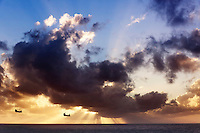 Two Chinook helicopters flying over the Pacific ocean at sunrise.
