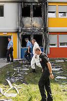 Brandanschlag auf Fluechtlingsunterkunft in Berlin-Buch.<br /> Am Montag den 8. August 2016 veruebten Unbekannte gegen 3.00 Uhr einen Brandanschlag auf eine Fluechtlingsunterkunft in Berlin-Buch. Sie warfen einen Molotowcoctail durch ein Fenster in das Haus und setzten das Gebaeude in Brand. Die Flammen schlugen bis in den zweiten Stock des Wohncontainers. Die Bewohner retteten schlafende Bewohner aus den oberen Stockwerken und <br /> loeschten den Brand selber mit Feuerloeschern bevor Feuerwehr und die Polizei kamen. Nach Angaben von Bewohnern muessen jetzt wahrscheinlich 180 Menschen aus den Wohncontainern ausziehen, da die Elektrik durch den Brand schwer beschaedigt wurde.<br /> Im Bild: Polizeibeamte einer Kriminalteschnischen Untersuchungseinheit (KTU) nach der Untersuchung der Brandstelle.<br /> 8.8.2016, Berlin<br /> Copyright: Christian-Ditsch.de<br /> [Inhaltsveraendernde Manipulation des Fotos nur nach ausdruecklicher Genehmigung des Fotografen. Vereinbarungen ueber Abtretung von Persoenlichkeitsrechten/Model Release der abgebildeten Person/Personen liegen nicht vor. NO MODEL RELEASE! Nur fuer Redaktionelle Zwecke. Don't publish without copyright Christian-Ditsch.de, Veroeffentlichung nur mit Fotografennennung, sowie gegen Honorar, MwSt. und Beleg. Konto: I N G - D i B a, IBAN DE58500105175400192269, BIC INGDDEFFXXX, Kontakt: post@christian-ditsch.de<br /> Bei der Bearbeitung der Dateiinformationen darf die Urheberkennzeichnung in den EXIF- und  IPTC-Daten nicht entfernt werden, diese sind in digitalen Medien nach §95c UrhG rechtlich geschuetzt. Der Urhebervermerk wird gemaess §13 UrhG verlangt.]