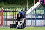 "© Joel Goodman - 07973 332324 . Stockport , UK . Veterinary surgeon SIMON CONSTABLE reaches past his dart gun for a stethoscope . A wild deer which was discovered in a park by the busy Manchester Road in Stockport has been rescued after three days . The park was closed and locked by Stockport Council officials on Monday 24th June after the young male started bolting across the playing field and playground and butting its head and antlers against railings . But with the gates locked , the young animal could not escape . For three days local people came out to watch the deer from the fence as it hid in bushes around the edge of the park , occasionally venturing out across the playing pitch and in the direction of the busy A626 road . The landlord at "" The Hind's Head "" pub opposite , Stuart Kirkham , a Manchester United fan , named the beast "" Ronaldo "" because of its red colouring . After three days , with no hope of escape under its own steam and with the park still closed , the RSPCA and council brought in a veterinary surgeon to help . The animal was tranquilised and driven to nearby Reddish Vale Country Park , where he was brought round and released back in to the wild . Photo credit : Joel Goodman"