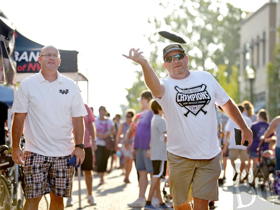 NWA Democrat-Gazette/BEN GOFF &bull; @NWABENGOFF<br /> Jonathon Guthrie (left) Bentonville West High School principal, takes on Bentonville High Principal Jack Loyd in a game of cornhole on Friday Aug. 7, 2015 during the Back to School Celebration First Friday on the Bentonville square. Guthrie and Bentonville West football coach Bryan Pratt defeated Loyd and Bentonville football coach Jody Grant 21-9.