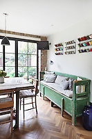 A rustic green bench with a hindged seat is a useful additonal storage area in Kally Ellis's kitchen