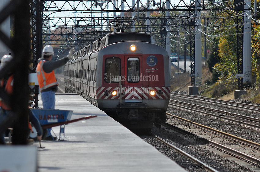Flagman Waves to Moving Metro-North Train at the Under Construction Railroad Station at Fairfield Metro Center CT on the Northeast Corridor.