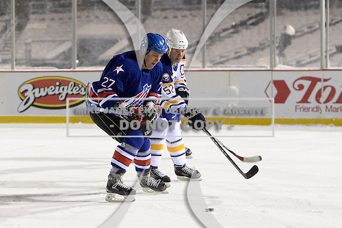 Dan Frawley (27) and Craig Rivet (52) battle for the puck during The Frozen Frontier Buffalo Sabres vs. Rochester Amerks Alumni Game at Frontier Field on December 15, 2013 in Rochester, New York.  (Copyright Mike Janes Photography)